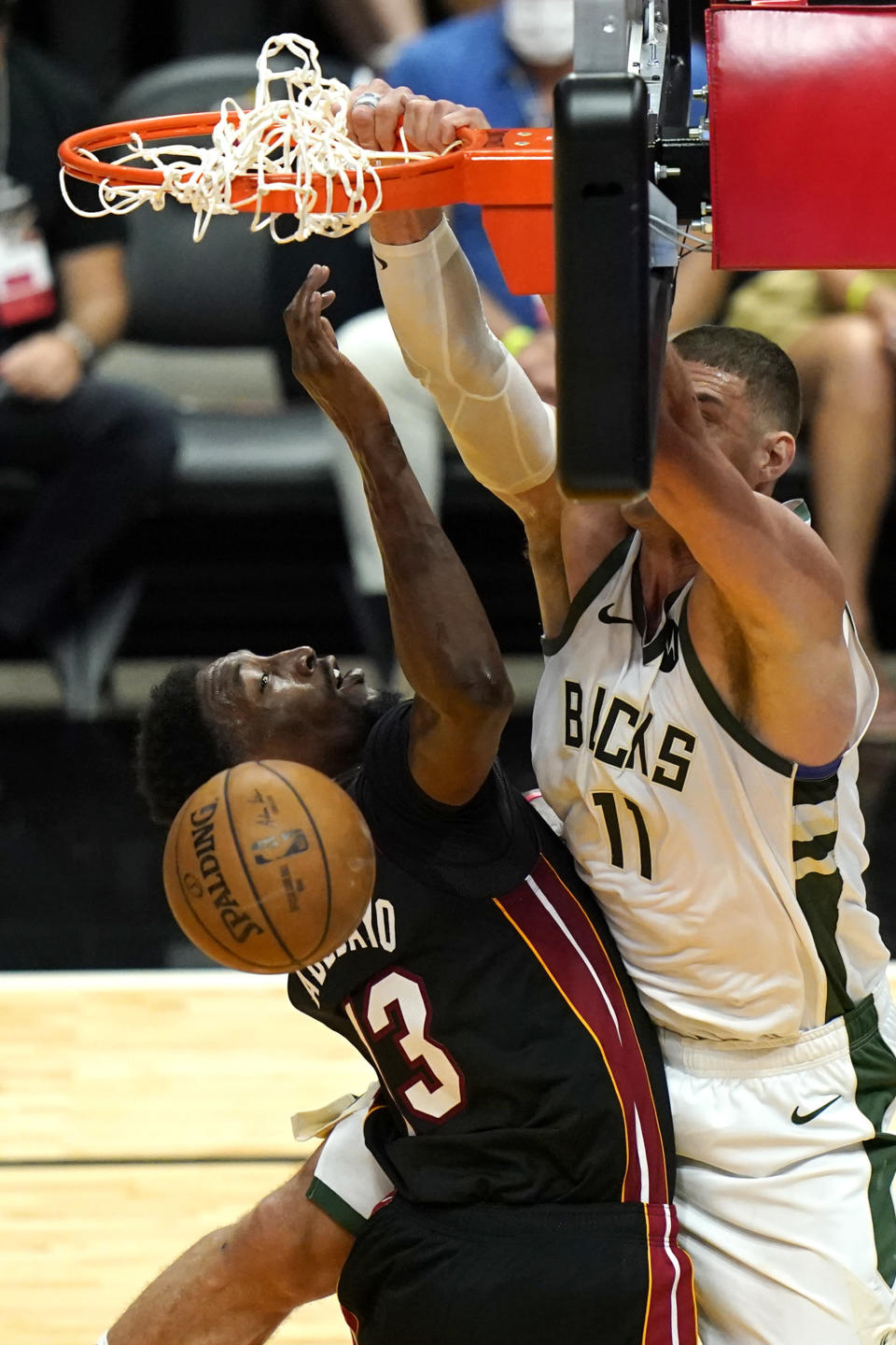 Milwaukee Bucks center Brook Lopez (11) dunks over Miami Heat center Bam Adebayo (13) during the second half of Game 4 of an NBA basketball first-round playoff series, Saturday, May 29, 2021, in Miami. The Bucks won 120-103. (AP Photo/Lynne Sladky)