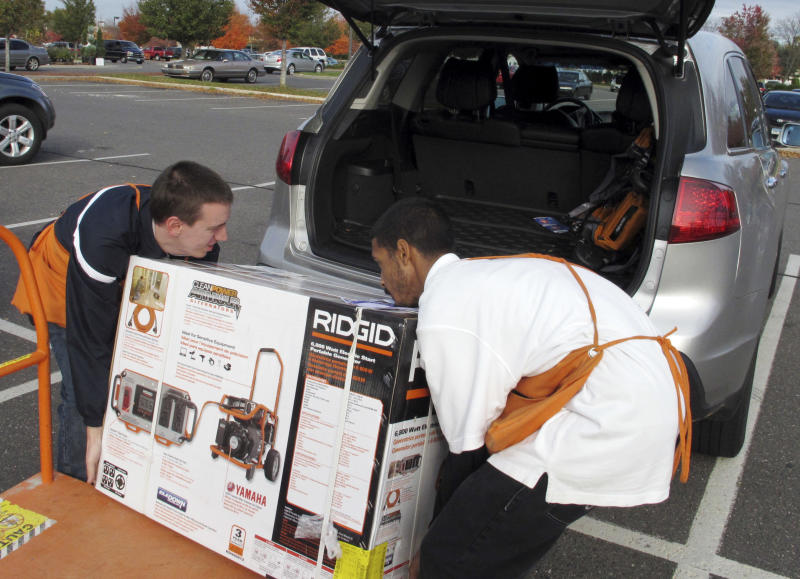 Home Depot workers Shaun Sika, left and Jose Maysonet load the last generator on the store's shelves into a customer's SUV in Glastonbury, Conn. on Thursday, Oct. 25, 2012. East Coast residents are preparing for a major storm expected to hit the region early next week. (AP Photo/Dave Collins)