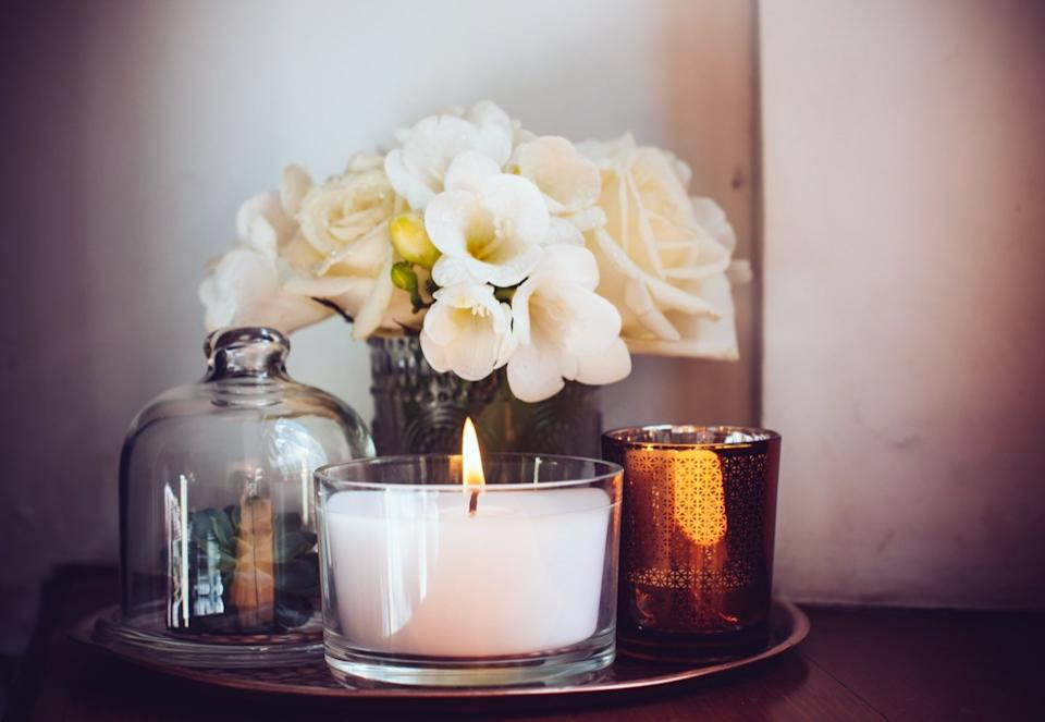 white candle in glass jar on tray