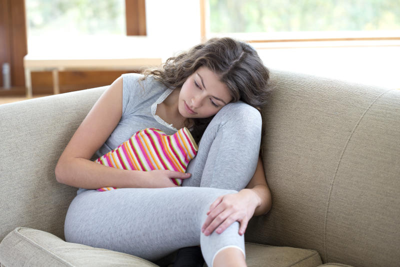 Woman on the couch with a hot water bottle