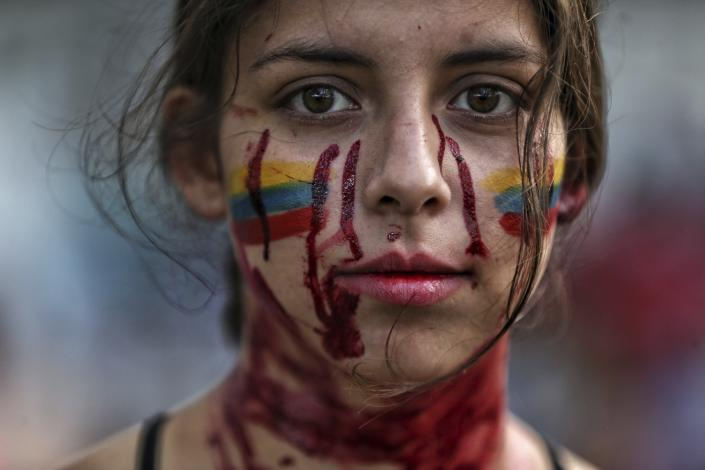 """A student performs a play called """"Who killed them"""" during anti-government protests in Cali, Colombia, Tuesday, May 11, 2021. Colombians have protested across the country against a government they feel has long ignored their needs, allowed corruption to run rampant and is so out of touch that it proposed tax increases during the coronavirus pandemic. (AP Photo/Andres Gonzalez)"""