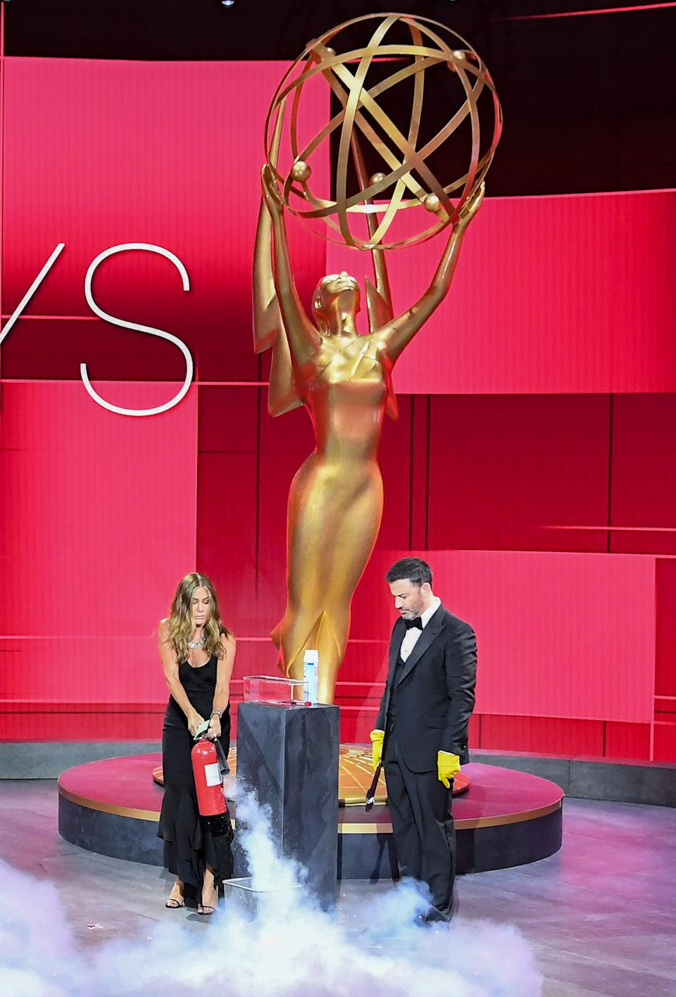 Jennifer Aniston and Jimmy Kimmel make sure the winner's envelope is fully sanitized before presenting the first award at the 72nd Primetime Emmys. (ABC/Image Group)