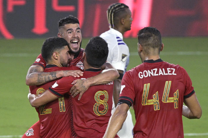 Toronto FC midfielder Jonathan Osorio (21) is congratulated by midfielder Alejandro Pozuelo, second from left, midfielder Mark Delgado (8) and defender Omar Gonzalez (44) after Osorio scored a goal during the first half of the team's MLS soccer match against Orlando City, Saturday, June 19, 2021, in Orlando, Fla. (AP Photo/Phelan M. Ebenhack)