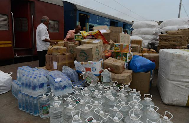 Indian workers load packaged water bottles and relief supplies onto a carriage of the 'Ahmedabad-Haridwar Mail' train at Kalupur railway station in Ahmedabad on June 25, 2013. Two truck loads of relief material including packaged water, dry snacks, clothes and other items which have been donated have been dispatched from Ahmedabad to Haridwar for flood survivors in the northern Indian state of Uttarakhand. AFP PHOTO/Sam PANTHAKY