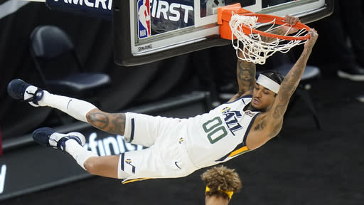 Utah Jazz guard Jordan Clarkson (00) hangs from the rim after dunking against the Golden State Warriors during the first half of an NBA basketball game Saturday, Jan. 23, 2021, in Salt Lake City. (AP Photo/Rick Bowmer)