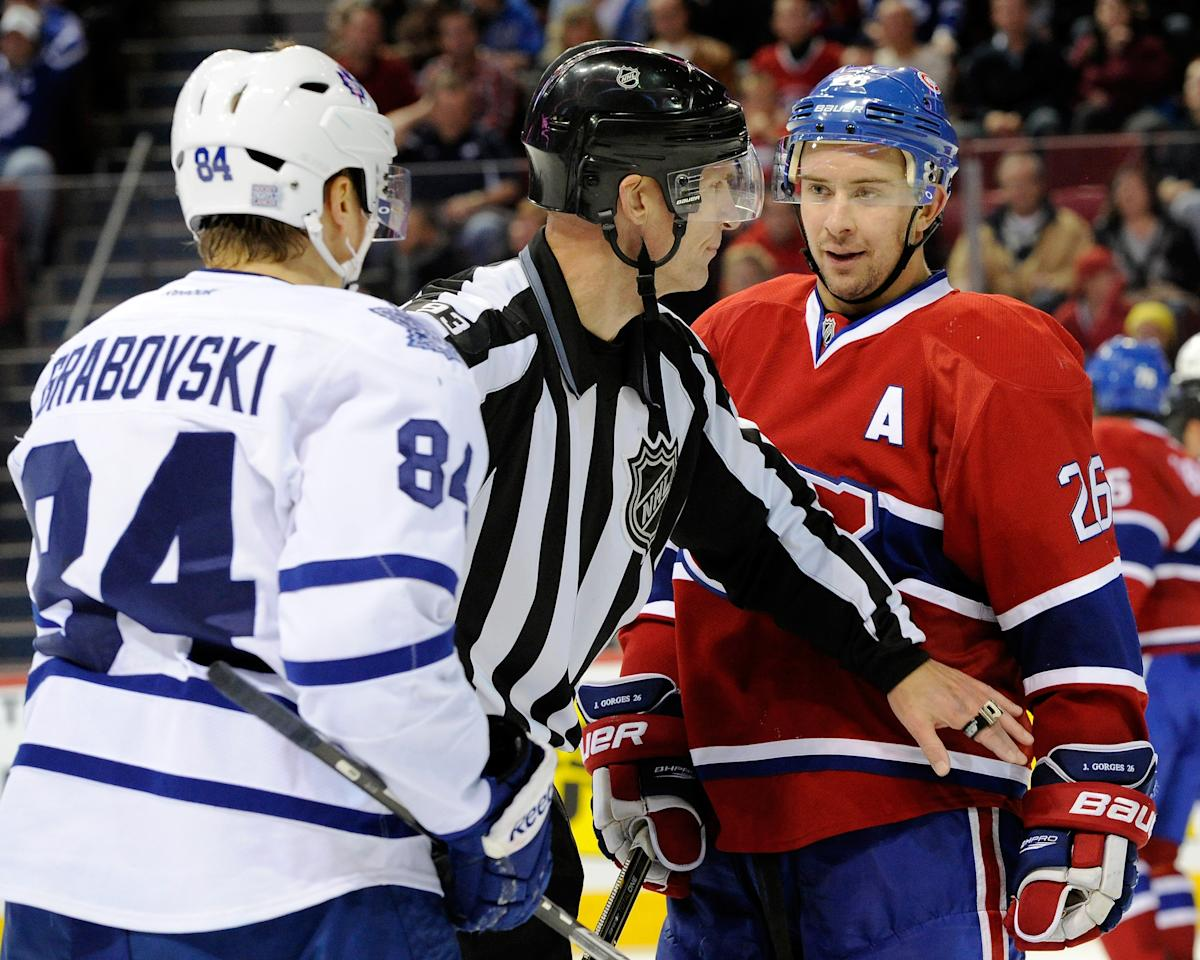MONTREAL, CANADA - OCTOBER 22: NHL linesman Brian Murphy #93 separates Josh Gorges #26 of the Montreal Canadiens and Mikhail Grabovski #84 of the Toronto Maple Leafs after a play stoppage during the NHL game at the Bell Centre on October 22, 2011 in Montreal, Quebec, Canada.  The Maple Leafs defeated the Canadiens 5-4 in overtime.  (Photo by Richard Wolowicz/Getty Images)