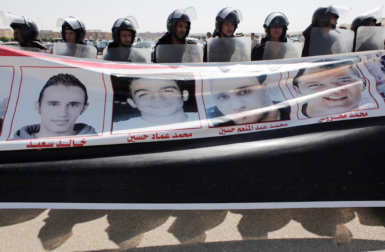 Egyptian riot police line up behind a banner with pictures of men killed during the revolution carried by anti-Mubarak protesters, outside the Police Military Academy complex in Cairo, Egypt Wednesday, Aug. 3, 2011, during the trial session of Egypt's ousted President Hosni Mubarak.  Mubarak was wheeled into a Cairo courtroom on a gurney Wednesday at the start of his historic trial on charges of corruption and ordering the killing of protesters during the uprising that ousted him. The scene, shown live on Egypt's state TV, was Egyptians' first look at their former president since Feb. 10, the day before his fall when he gave a defiant speech refusing to resign. (AP Photo/Nasser Nasser)