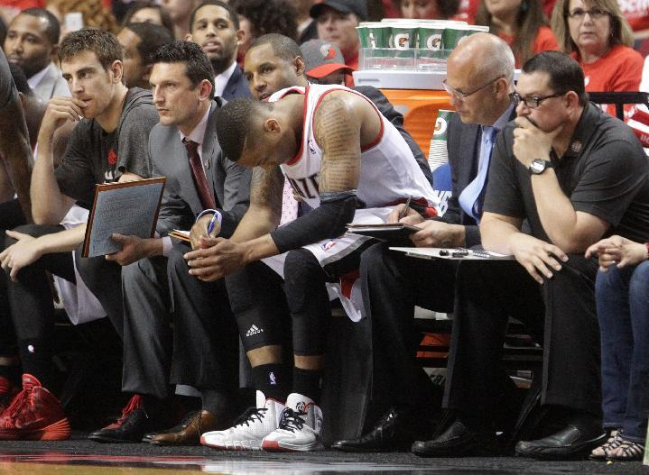 Portland Trail Blazers' Damian Lillard, center, sits on the bench near the end of Game 3 of a Western Conference semifinal NBA basketball playoff series against the San Antonio Spurs, Saturday, May 10, 2014, in Portland, Ore. The Spurs won 118-103