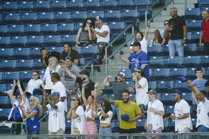 Relatives and loved ones of Toronto Blue Jays' Alek Manoah cheer during the fifth inning of the first game of a baseball doubleheader against the New York Yankees Thursday, May 27, 2021, in New York. (AP Photo/Frank Franklin II)