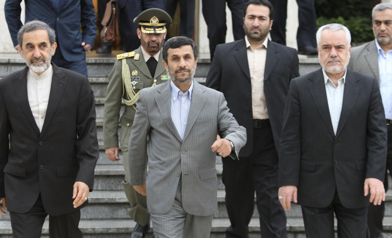 CORRECTS VICE PRESIDENT'S NAME TO RAHIMI - Iranian President Mahmoud Ahmadinejad, center, makes his way during a departure ceremony for him as he leaves the country for Turkey to attend an international conference, as Vice President Mohammad Reza Rahimi, right, and advisor to the supreme leader, Ali Akbar Velayati, left, walk at the Mehrabad airport in Tehran, Iran, Monday, May 9, 2011. (AP Photo/Vahid Salemi)
