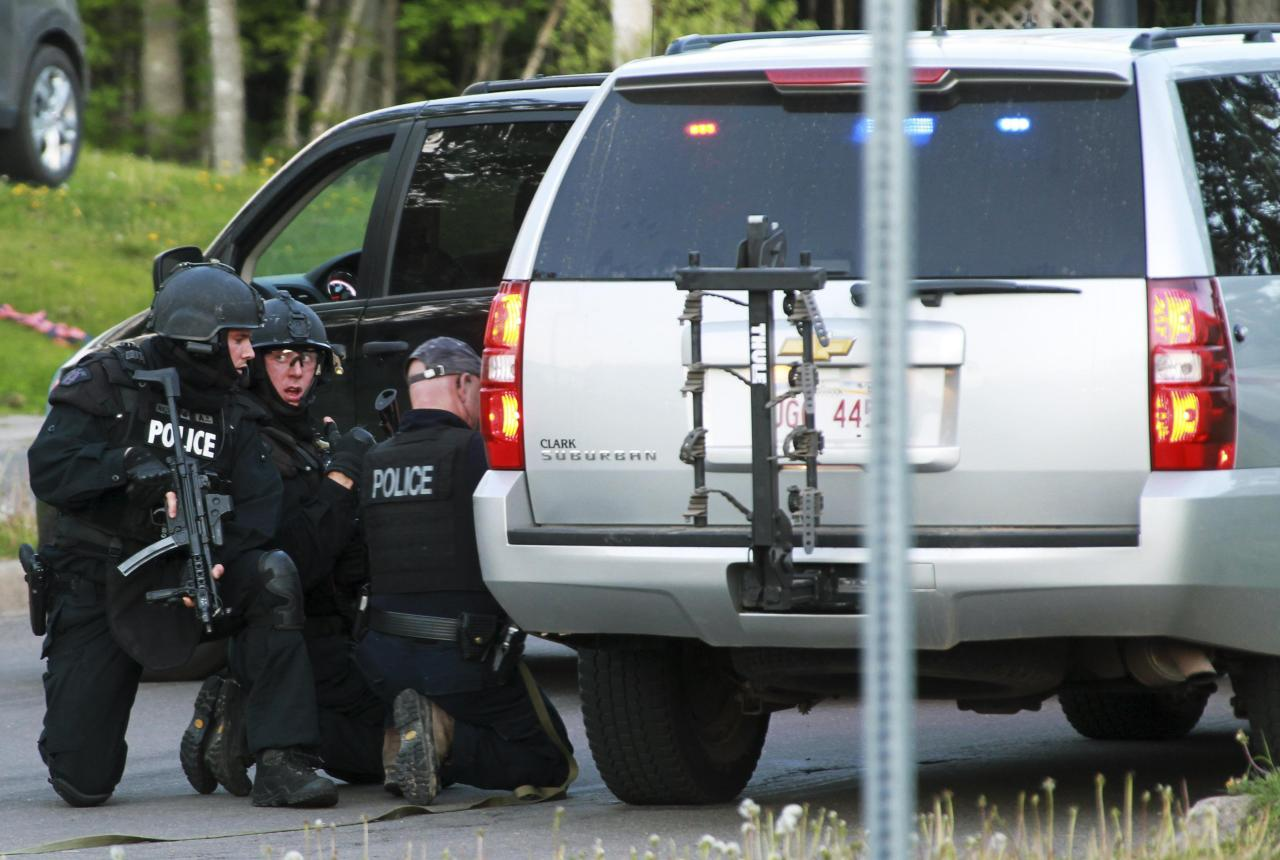 Emergency Response team members take cover behind vehicles in Moncton, New Brunswick June 4, 2014. Three police officers were shot dead and two more were wounded, police said as they conducted a manhunt for a man carrying a rifle and wearing camouflage clothes. Police said they were searching for Justin Bourque, 24, of Moncton. REUTERS/Ron Ward/Moncton Times & Transcript (CANADA - Tags: CRIME LAW TPX IMAGES OF THE DAY) FOR EDITORIAL USE ONLY. NOT FOR SALE FOR MARKETING OR ADVERTISING CAMPAIGNS. NO ARCHIVES. NO SALES