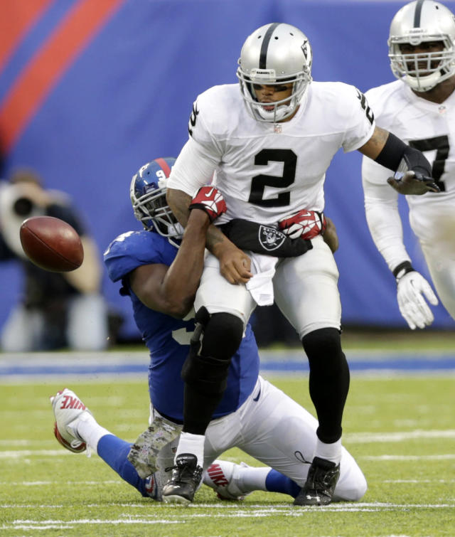Oakland Raiders quarterback Terrelle Pryor (2) fumbles the ball after being hit by New York Giants defensive end Mathias Kiwanuka during the second half of an NFL football game on Sunday, Nov. 10, 2013, in East Rutherford, N.J. The Giants won 24-20. (AP Photo/Kathy Willens)