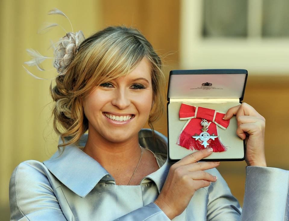 British actress Brooke Kinsella proudly holds her MBE, after it was presented to her by the Prince of Wales during the Investiture Ceremony at Buckingham Palace in central London on December 14, 2011. AFP PHOTO/POOL/ John Stillwell (Photo credit should read JOHN STILLWELL/AFP/GettyImages)