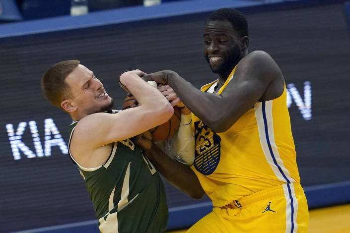 Milwaukee Bucks guard Donte DiVincenzo, left, tries to control the ball against Golden State Warriors forward Draymond Green during the first half of an NBA basketball game in San Francisco, Tuesday, April 6, 2021. (AP Photo/Jeff Chiu)