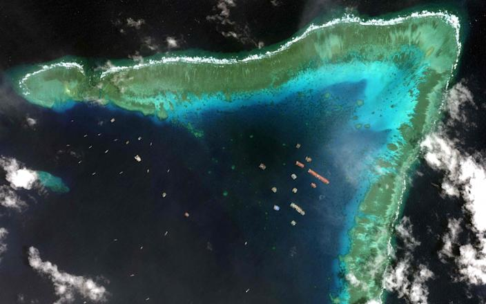 Chinese vessels anchored at the Whitsun Reef, around 175 nautical miles west of Bataraza in Palawan in the South China Sea. The boats gathered near a disputed reef in the South China Sea are 'fishing boats' sheltering from poor weather, the China foreign ministry said March 22, a day after the Philippines described their presence as an incursion - AFP