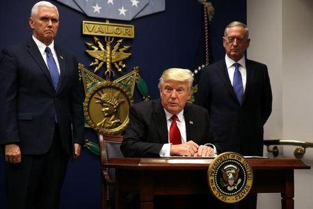 U.S. President Donald Trump signs an executive order to impose tighter vetting of travelers entering the United States, at the Pentagon in Washington