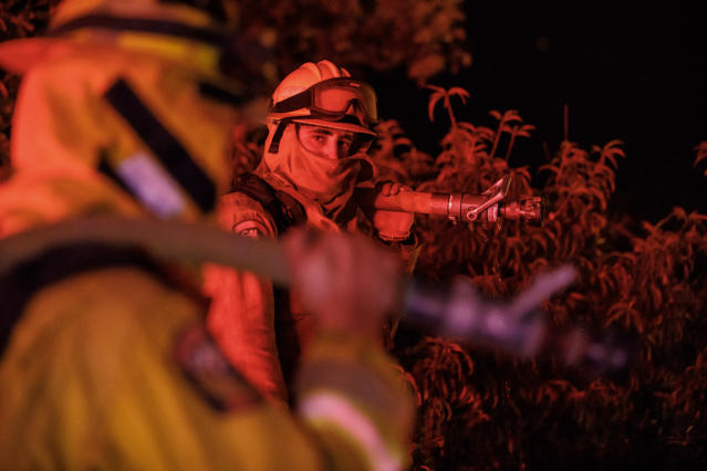 <p>Firefighters performing structure protection in the mountains above Lake Elsinore, Calif., on Aug. 10, 2018. (Photo: Marcus Yam/Los Angeles Times via Getty Images) </p>