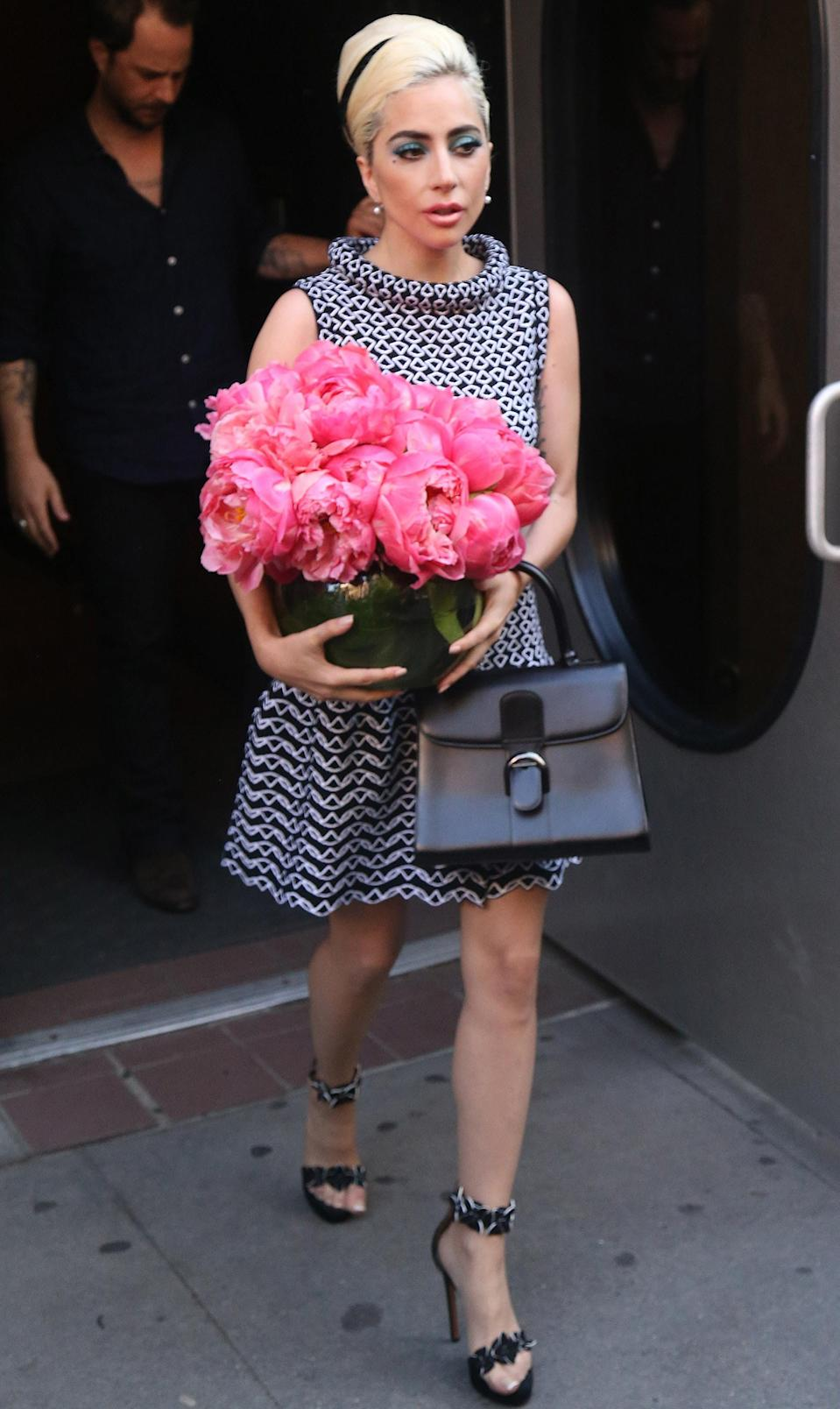 <p>She then took an elegant leap into the sixties with a turtleneck dress, matching heels and a bunch of hot pink flowers. [Photo: Rex] </p>