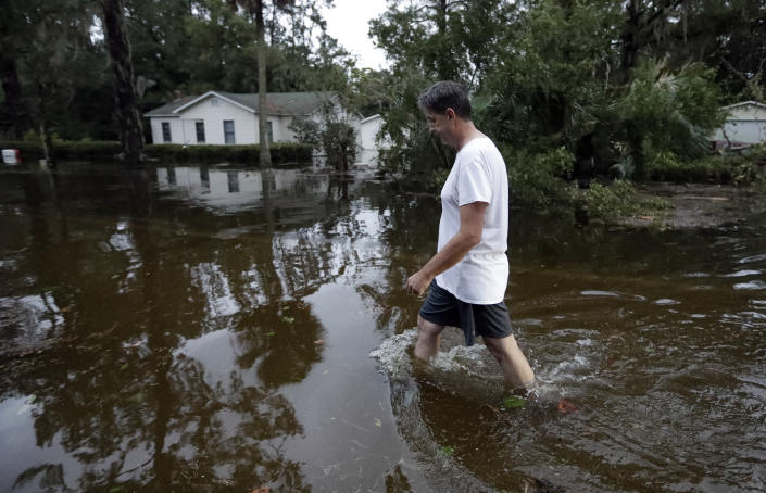 <p>John Gouge walks through flood waters as he goes to check on the post office Wednesday, Oct. 10, 2018, in St. Marks, Fla. (Photo: Chris O'Meara/AP) </p>