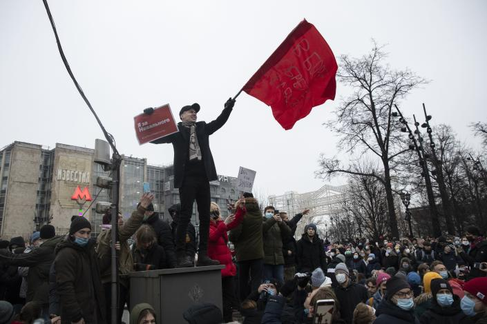 "FILE - In this Jan. 23, 2021, file photo, a demonstrator waves a red flag and holds a banner that reads: ""I'm for Navalny,"" at a protest supporting jailed opposition leader Alexei Navalny in Moscow, Russia. Rattled by the nationwide demonstrations supporting him, Russian authorities are moving rapidly to block any new ones – from piling legal pressure on his allies to launching a campaign to discredit the rallies. (AP Photo/Pavel Golovkin, File)"