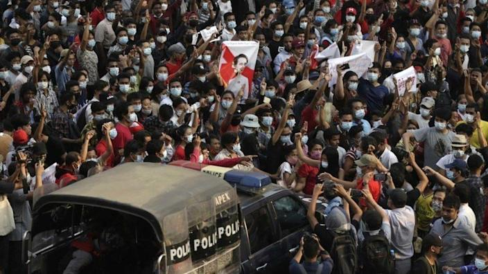 A police vehicle makes its way through a demonstration against the military coup, in Yangon, Myanmar