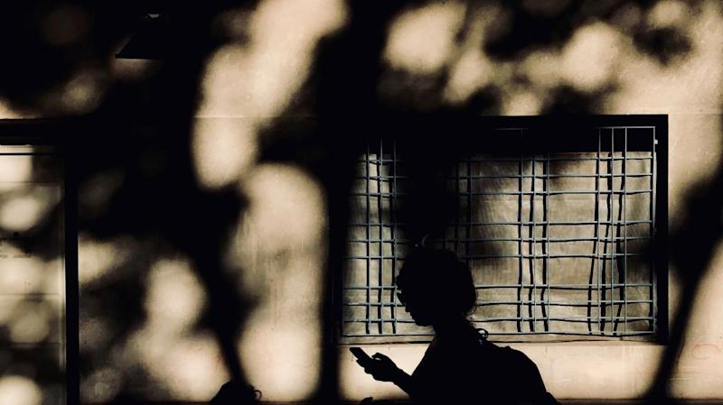A woman is silhouetted as she looks at her cell phone.