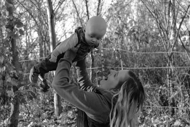 A mother is holding her baby up in the air