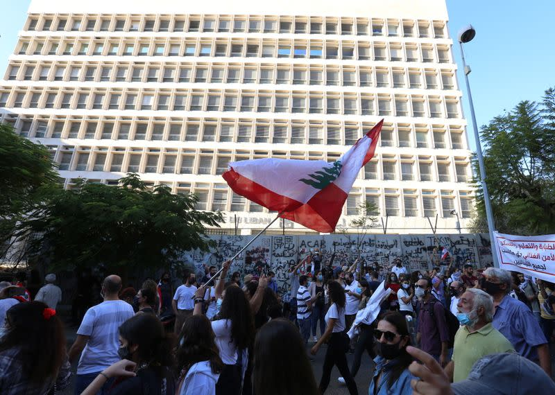 An anti-government demonstrator holds a Lebanese flag during a protest as Lebanese mark one year since the start of nation-wide protests, in front of the central bank building in Beirut