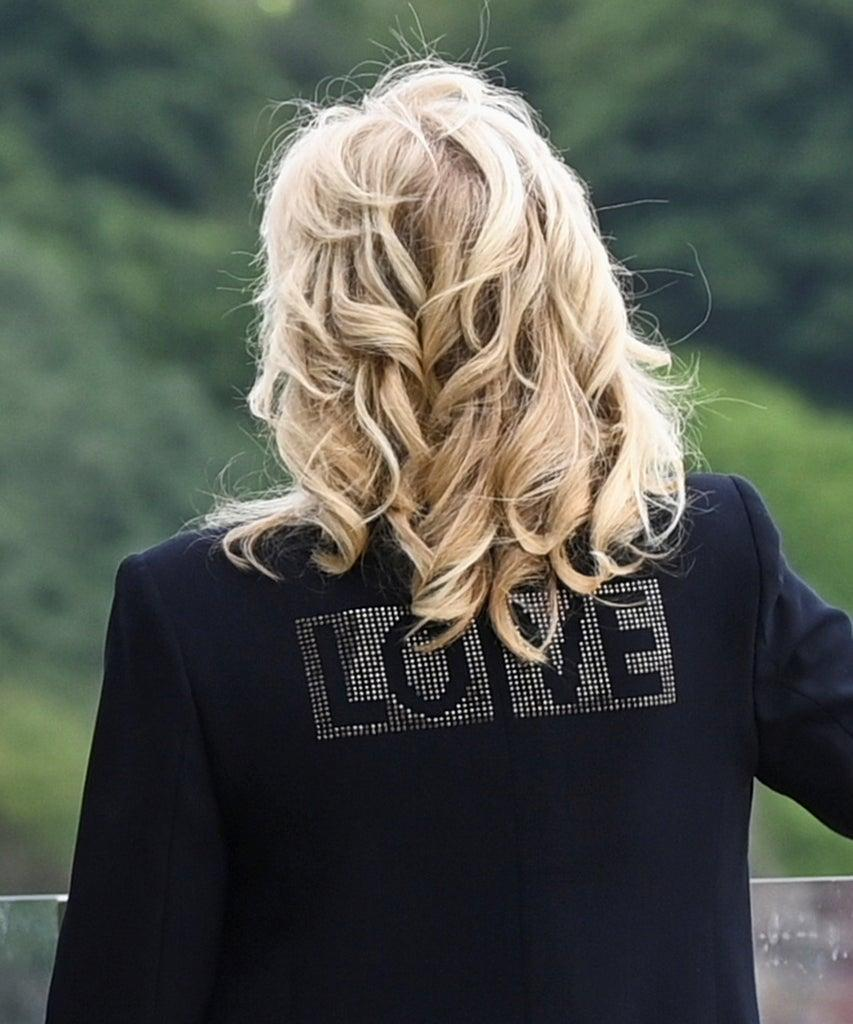"""ST IVES, ENGLAND – JUNE 10: First Lady Jill Biden, wearing a jacket with the phrase """"Love"""" on the back, stands outside the Carbis Bay Hotel on June 10, 2021 in St Ives, England. UK Prime Minister, Boris Johnson, will host leaders from the USA, Japan, Germany, France, Italy and Canada at the G7 Summit which begins on Friday, June 11 2021. (Photo by Toby Melville-WPA Pool/Getty Images)"""