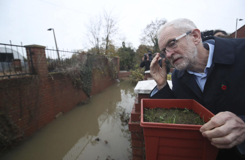 Labour leader Jeremy Corbyn looks at the effects of flooding during a visit to Conisborough, South Yorkshire, England, Saturday, Nov. 9, 2019. British political leaders swapped blame Saturday over floods that have drenched parts of England as the deluge became an issue in the campaign for the Dec. 12 election. (Danny Lawson/PA via AP)