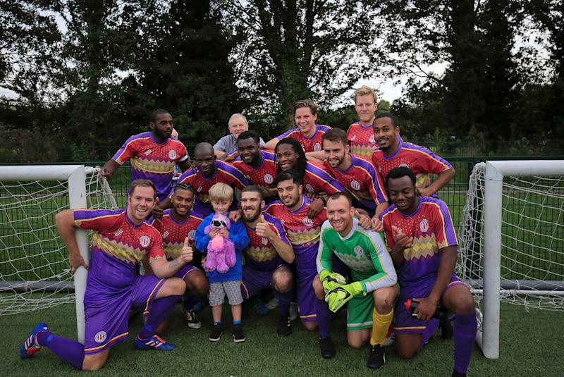 REFILE - CORRECTING SCORE AND TYPO  Clapton CFC players pose for a picture with one of their youngest supporter after winning 2-1 away game against Ealing Town in East Acton, in London, Britain September 15, 2018. Picture taken September 15, 2018. REUTERS/James Akena