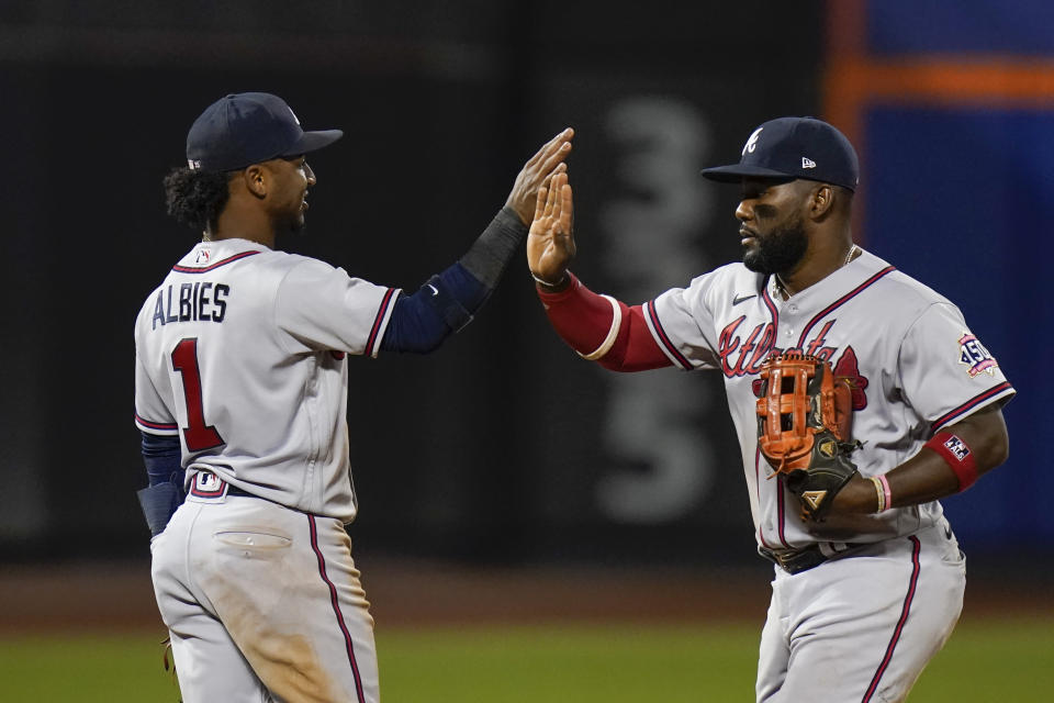 Atlanta Braves' Ozzie Albies, left, celebrates with teammte Abraham Almonte after a baseball game against the New York Mets, Tuesday, June 22, 2021, in New York. The Braves won 3-0. (AP Photo/Frank Franklin II)