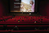 """French director Quentin Dupieux, and cast members Adele Exarchopoulos, David Marsais, and Gregoire Ludig, from left to right, attend the early first cinema screening and one year delay premiere of 'Mandibules' in Paris, Wednesday, May, 19, 2021. Cinemas, as café and restaurant terraces, museums, and theaters are reopening their doors after a shutdown of more than six months in the first stage of a government strategy to incrementally lift restrictions to stave off COVID-19, and give the French back some of their signature """"joie de vivre."""" (AP Photo/Francois Mori)"""