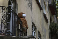 A teddy bear wearing a face mask hangs from a balcony in Mexico City, Thursday, April 9, 2020, as many stay indoors amid the spread of the new coronavirus. (AP Photo/Fernando Llano)