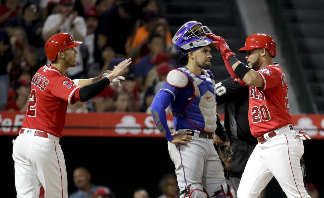 Los Angeles Angels' Jose Fernandez, right, celebrates after his two-run home run with Andrelton Simmons, left, as Texas Rangers catcher Robinson Chirinos look000s away during the third inning of a baseball game in Anaheim, Calif., Wednesday, Sept. 12, 2018. (AP Photo/Chris Carlson)