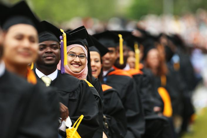 Students graduate at City College on June 3, 2016, in New York City. The debt many grads face right out of college has continued to climb.