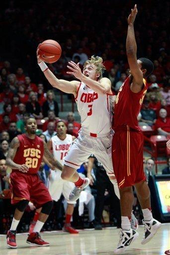 New Mexico's Hugh Greenwood, left, scores 2 of his game-high 17 points against Southern California's Eric Wise in the first half of an NCAA college basketball game at The Pit in Albuquerque, N.M. Wednesday, Dec. 5, 2012. New Mexico won 75-67. (AP Photo/Eric Draper)