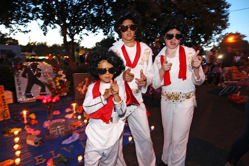 Nicholas Woodlief, 7, left, his sister Annabelle Woodlief, 11, and friend, Eli Crain, 11, right, strike an Elvis Presley pose at Graceland, Presley's home, before the annual candlelight vigil on Thursday, Aug. 15, 2013, in Memphis, Tenn. Presley fans from around the world made their annual pilgrimage to Graceland to pay their respects to the rock n' roll icon with a solemn candlelight vigil on the 36th anniversary of his death. (AP Photo/The Commercial Appeal, Nikki Boertman)