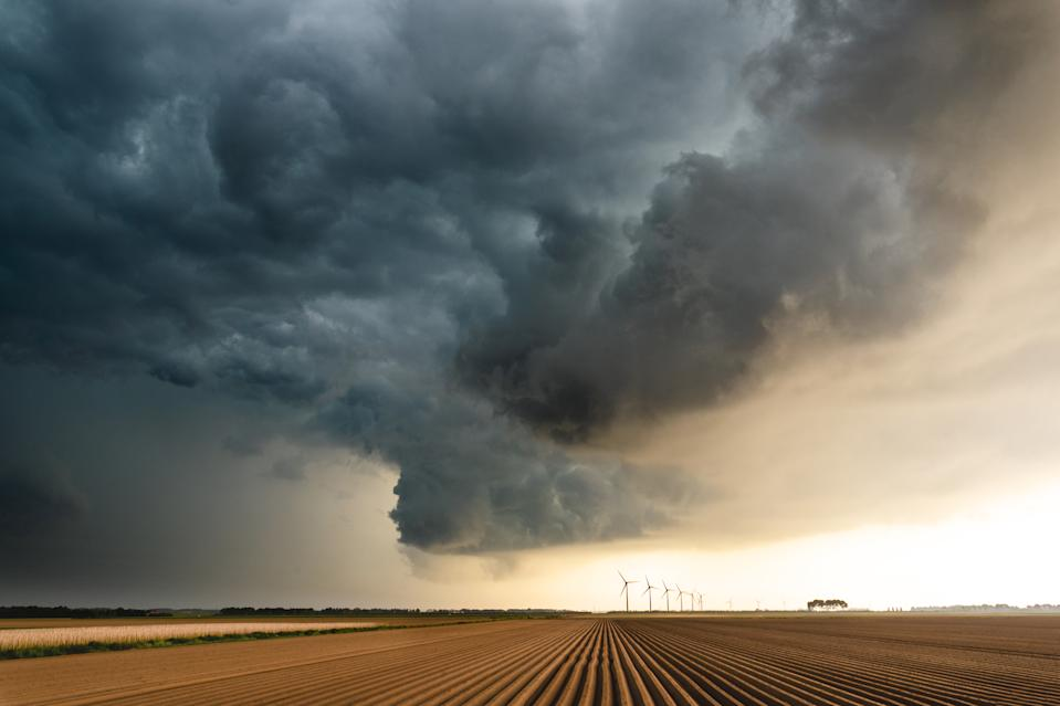 This is a picture of a storm as it is building up over an uncultivated  agricultural field and some wind turbines in the horizon. It was shot at a location in the eastern part of the Netherlands.