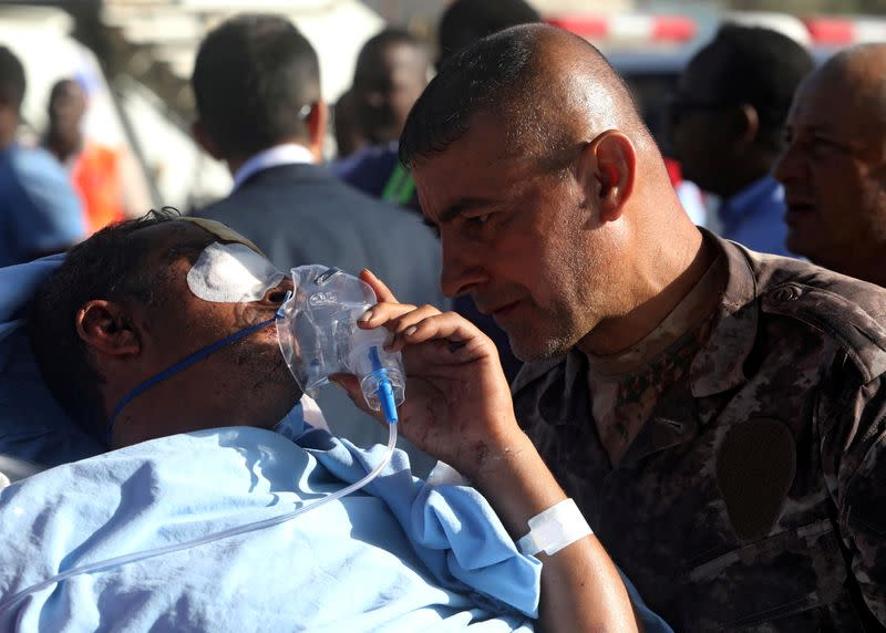 A Turkish military officer talks to a Turkish worker injured in an explosion in Afgoye town, before he boards a Turkish military cargo plane at the Aden Abdulle International Airport in Mogadishu