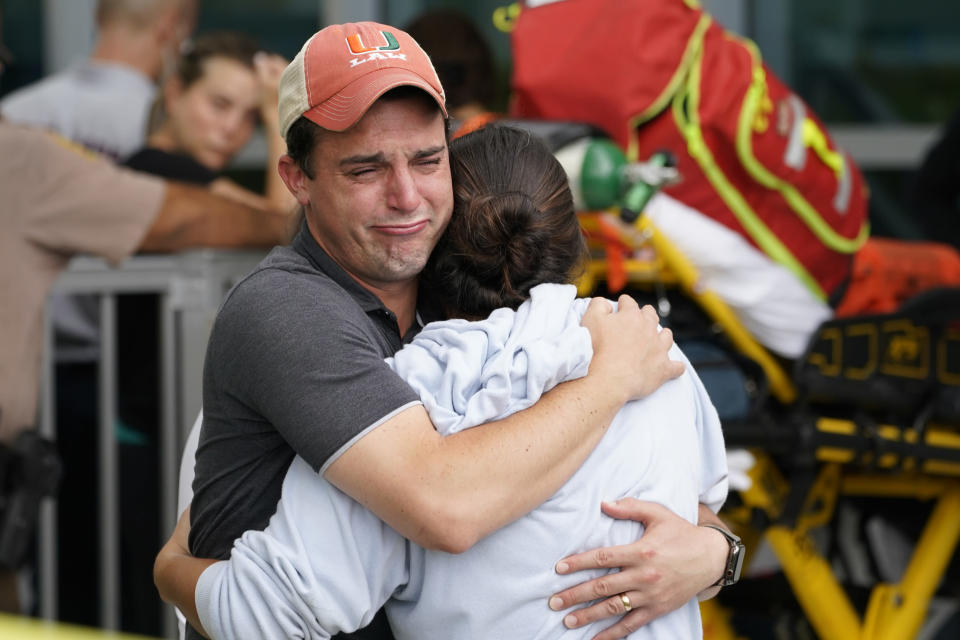 A couple embrace as they wait for news of survivors from a condominium that collapsed, Thursday, June 24, 2021 in Surfside, Fla. Dozens of survivors were pulled out, and rescuers continue to look for more. (AP Photo/Marta Lavandier)