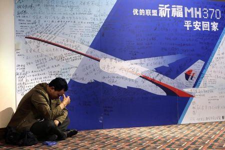 A man pauses as he smokes next to a message board dedicated to passengers onboard Flight MH370 at Lido Hotel in Beijing