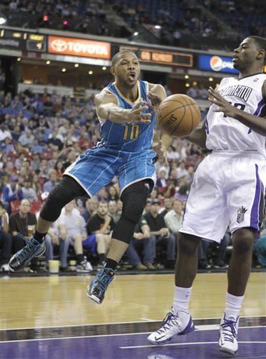 New Orleans Hornets guard Eric Gordon, left, passes against Sacramento Kings guard Tyreke Evans during the first quarter of an NBA basketball game in Sacramento, Calif., Wednesday, April 10, 2013. (AP Photo/Rich Pedroncelli)
