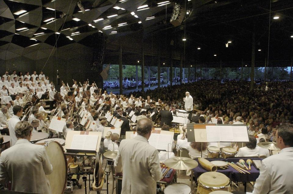 FILE - In this July 9, 2004 file photo, Kurt Masur conducts the Boston Symphony Orchestra on the season opening night at Tanglewood in Lenox, Mass. The Boston Symphony Orchestra announced Friday, March 19, 2021 that its 2021 outdoor season at Tanglewood, the acclaimed symphony's summer home in the Berkshires of western Massachusetts, will feature a return to live, in-person concerts from July 9 to Aug. 16. The event was canceled in 2020 due to the COVID-19 pandemic. (AP Photo/Paul Franz, File)