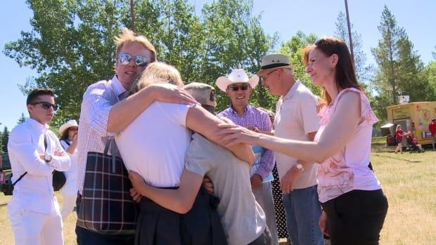 Health minister Tyler Shandro comforts his family after protesters cornered them at a Canada Day event.  (Helen Pike/CBC - image credit)