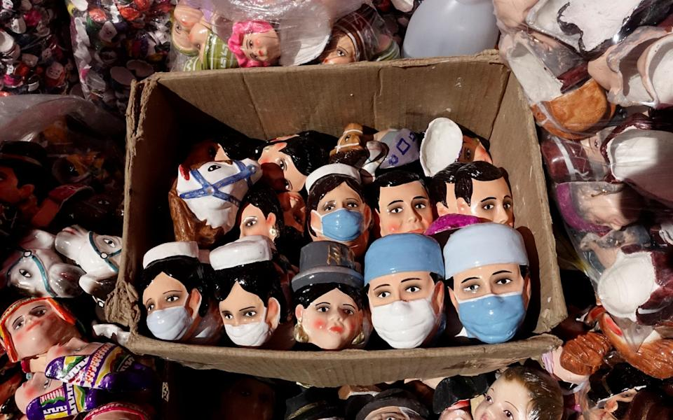 Masks for making Tanta Wawas (bread children) in honor of the victims of the coronavirus disease (COVID-19) are displayed at a market - DAVID MERCADO / REUTERS