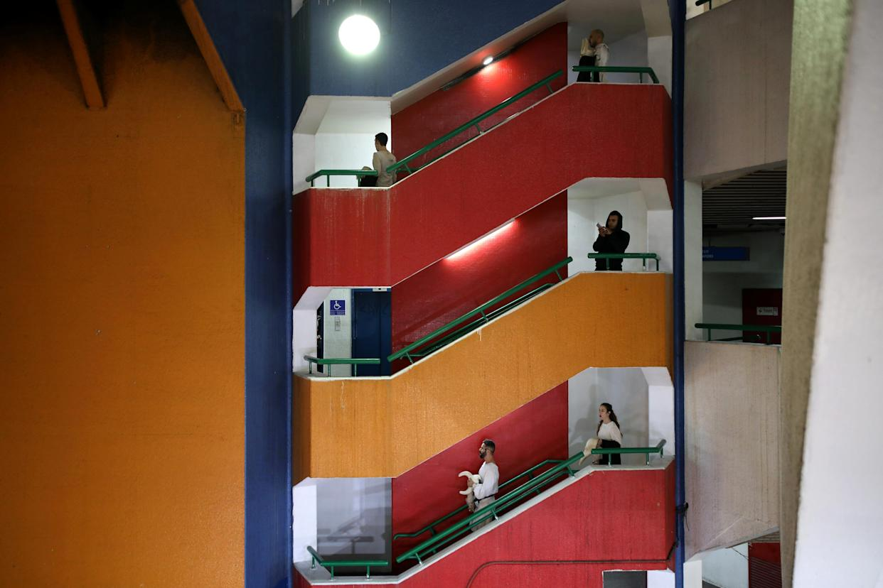 """Actors from the Mystorin Theatre Ensemble, and a passerby, walk down the stairs during the group's show """"Seven,"""" at the Central Bus Station on Dec. 27, 2018. (Photo: Corinna Kern/Reuters)"""