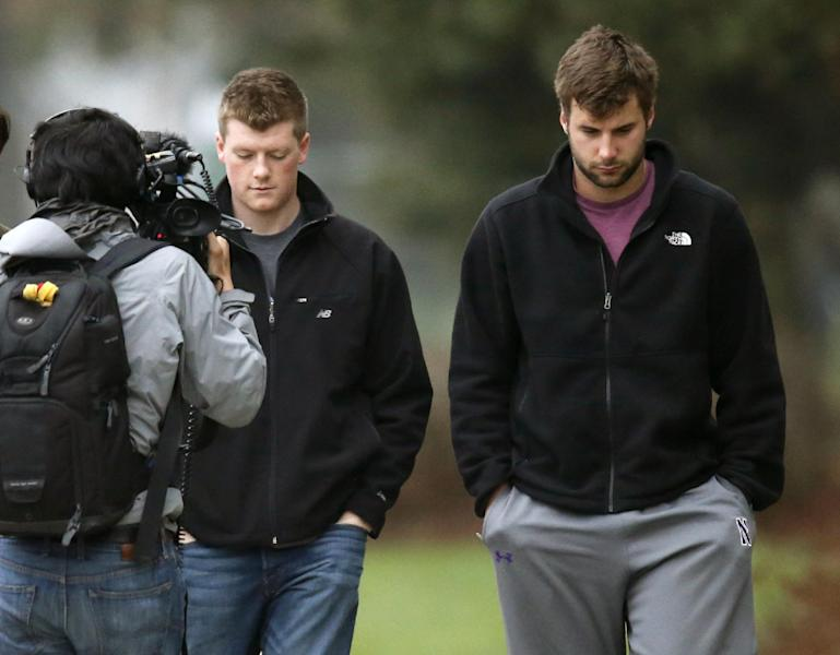 An unidentified Al Jazeera cameraman watches Northwestern football players Chris Gradone and Zach Oliver, right, as they walk to McGaw Hall where voting is taking place on the student athlete union question Friday, April 25, 2014, in Evanston, Ill. Northwestern football players cast secret ballots Friday in an on-campus hall adjacent to their home stadium on whether to form the nation's first union for college athletes. (AP Photo/Charles Rex Arbogast)