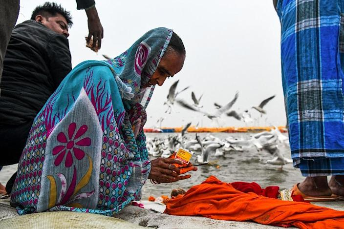 A devotee prays after taking a dip at the Triveni Sangam banks, the confluence of the Ganges, Yamuna and mythical Saraswati rivers (AFP Photo/CHANDAN KHANNA)
