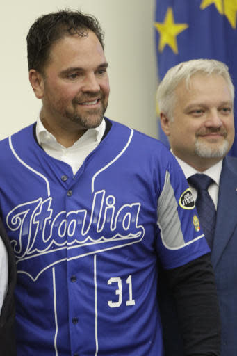 Hall of Fame catcher Mike Piazza shows his jersey during his presentation as Italy's national baseball team coach, at the Italian Olympic Committee headquarters in Rome, Friday, Nov. 29, 2019. At left is the President of the Italian Baseball Federation Andrea Marcon. (AP Photo/Alberto Pellaschiar)